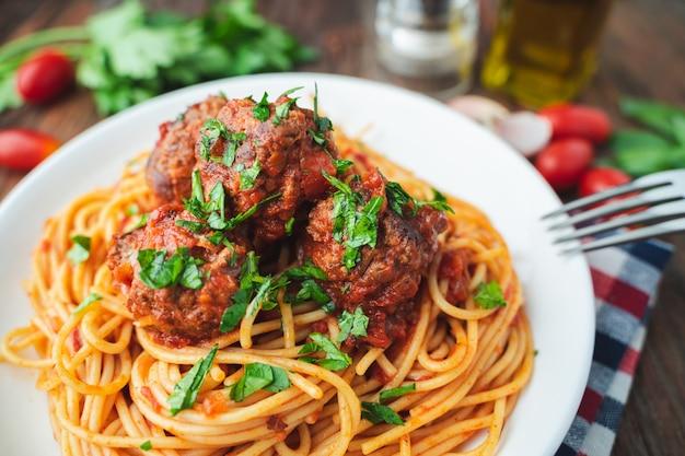 Spaghetti and meatballs with tomato sauce in white dish on wooden rustic board Premium Photo
