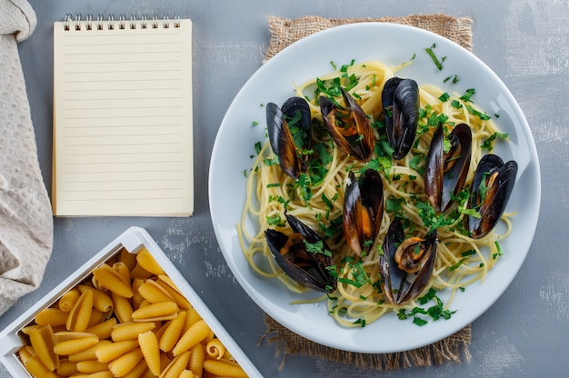 Spaghetti and mussel in a plate with copybook, raw pasta, kitchen towel Free Photo