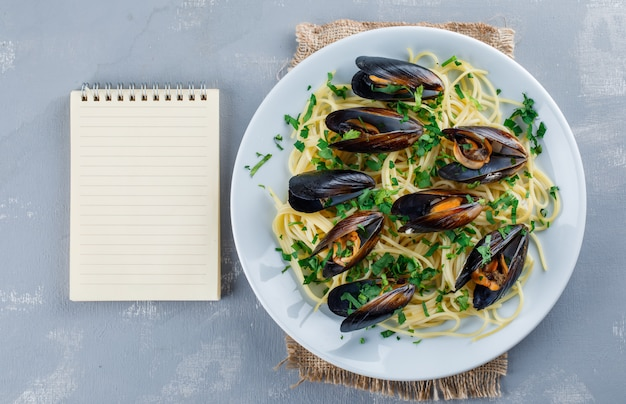 Spaghetti and mussel in a plate with copybook Free Photo