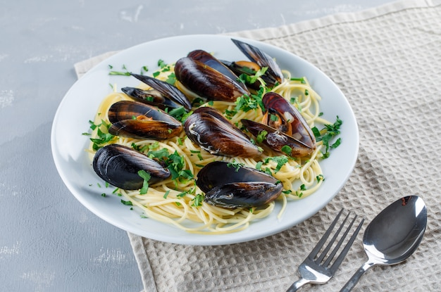Spaghetti and mussel with spoon, fork in a plate on plaster and kitchen towel Free Photo