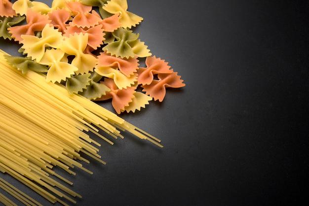 Spaghetti pasta and farfalle pasta on black kitchen counter Free Photo