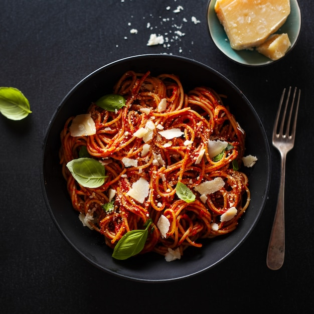 Spaghetti pasta with tomato sauce cheese and basil served in bowl. Premium Photo