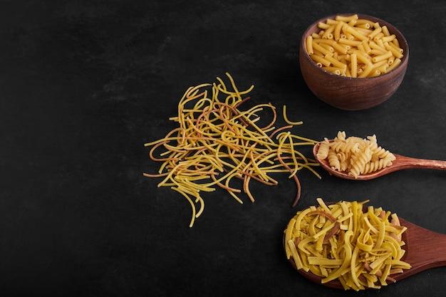 Spaghetti pieces on black background. Free Photo