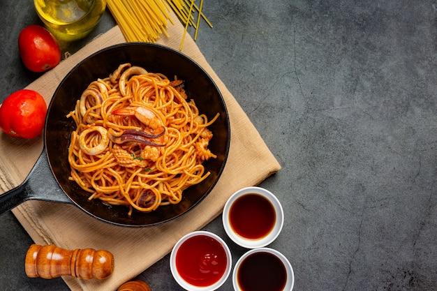 Спагетти с морепродуктами в томатном соусе, украшенные красивыми ингредиентами. Бесплатные Фотографии
