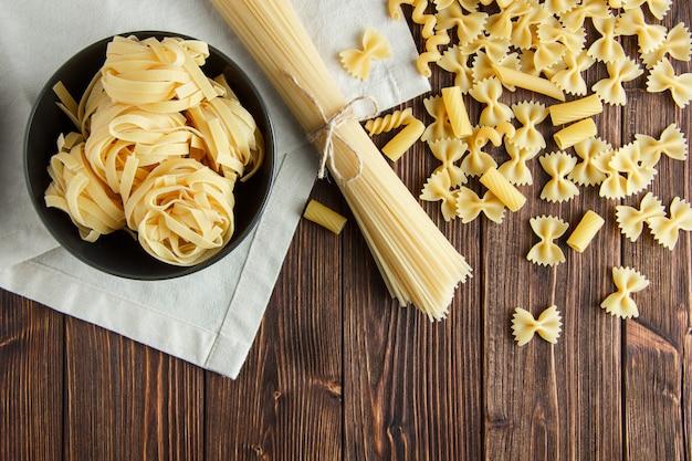 Спагетти с ассорти из сырых макаронных изделий на деревянных и кухонное полотенце фон, плоское положение. Бесплатные Фотографии