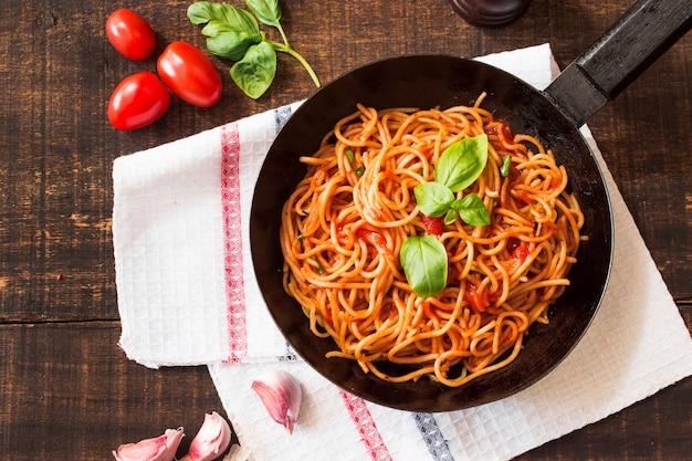 Spaghetti with basil leaf in frying pan on wooden table with ingredients Free Photo