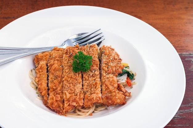 Спагетти с соусом из жареной свинины на тарелке Premium Фотографии
