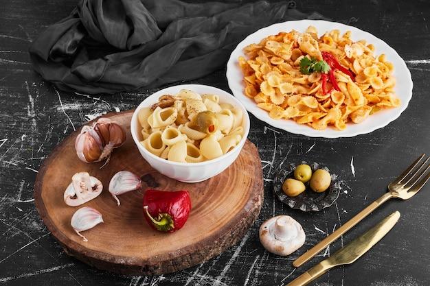 白い皿にハーブと野菜を入れ、カップにパスタを入れたスパゲッティ。 無料写真