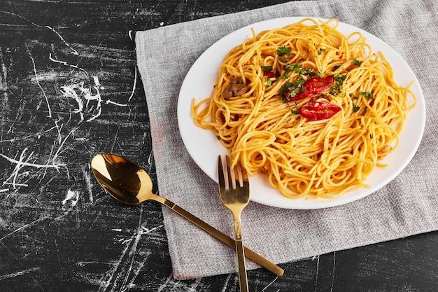 白いプレートにハーブと野菜のスパゲッティ、上面図 無料写真