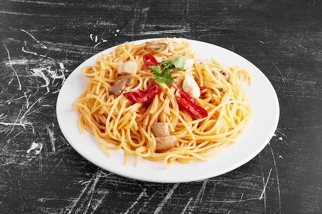 黒の背景、上面図の白いプレートに混合成分とスパゲッティ。 無料写真