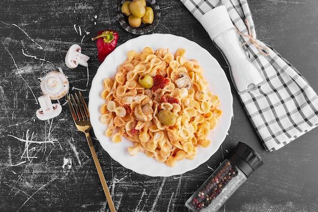 白いプレートに材料を混ぜたスパゲッティ、上面図。 無料写真