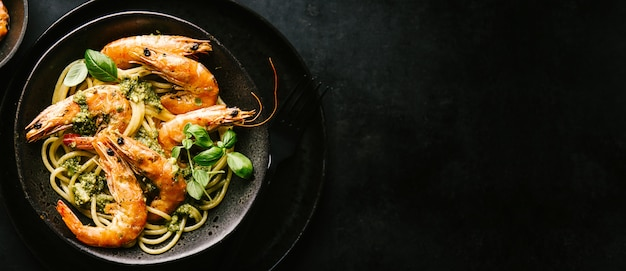 Spaghetti with pesto and prawns served on plate Free Photo
