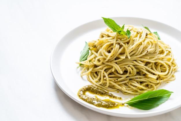 Spaghetti with pesto sauce, olive oil and basil leaves. Premium Photo