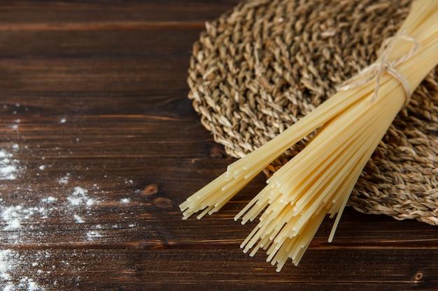 木製と籐のランチョンマットの背景、高角度のビューに小麦粉を振りかけたスパゲッティ。 無料写真