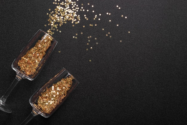 Spangles scattered from glasses on table Free Photo