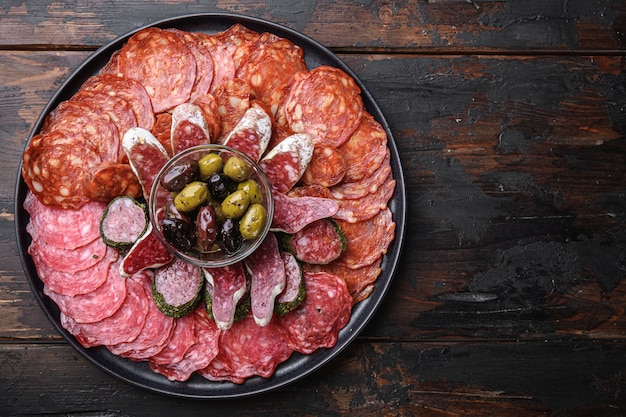 Spanish cold meat plate, chorizo, fuet, lomo, longaniza and salchichon on wooden table Premium Photo