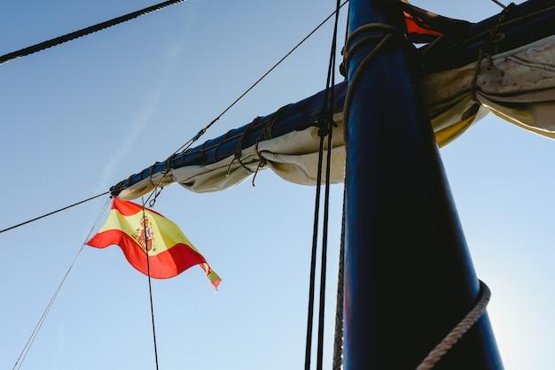 Spanish flag on commercial sailing ship. Premium Photo