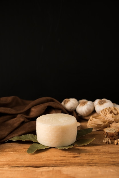 Spanish manchego cheese, bay leaves, raw pasta and garlic bulbs on wooden table Free Photo