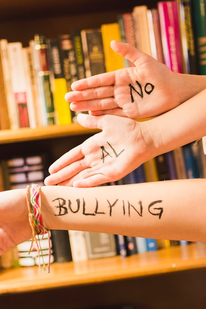 Spanish message against bullying on children's hands Free Photo