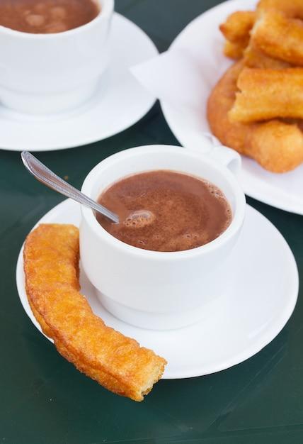 スペインのペストリー-チュロスとチョコレートのカップ Premium写真