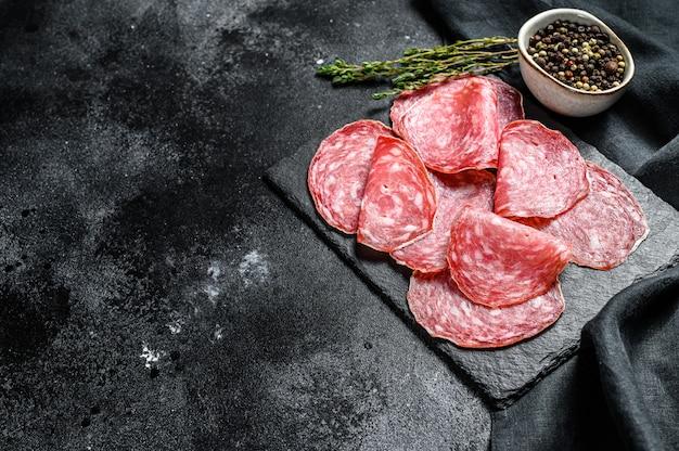 Spanish salami salchichon on a black chopping board. black background. top view. copy space Premium Photo