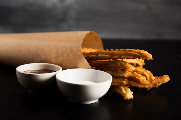 Spanish snack of churros and cups with melted chocolate and sugar Free Photo