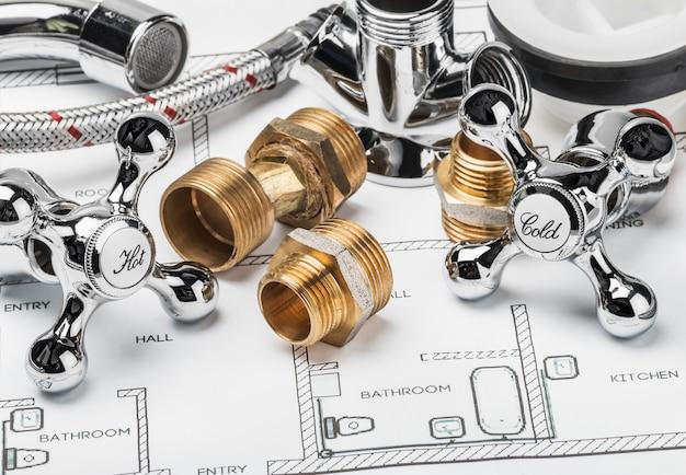 Запчасти и инструменты лежащие на чертеже для ремонта сантехники Premium Фотографии