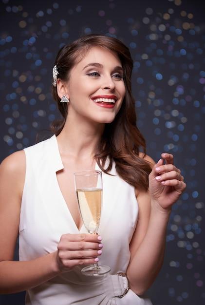 きらめく壁とシャンパンを持つ女性 無料写真