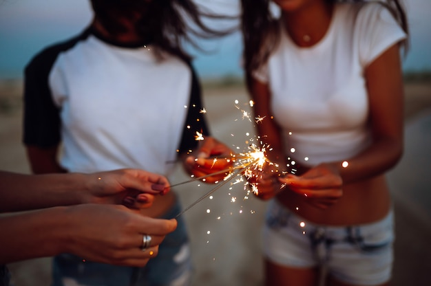 The sparklers in the hands of young girls on the beach ...