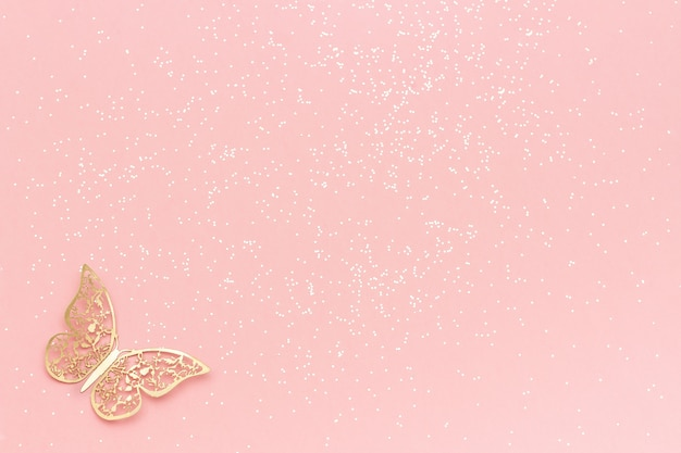 Sparkles glitter and gold tracery butterfly on pink pastel trendy background. festive background, template Premium Photo