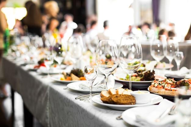 Игристые стеклянные изделия стоят на длинном столе, подготовленном к свадьбе di Бесплатные Фотографии