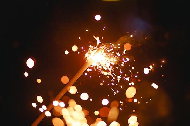 Искры и свет от бенгальских огней в темноте с ярко-желтым и оранжевым боке и дымом. праздничная текстура огня, фон на новый год и рождество. Premium Фотографии