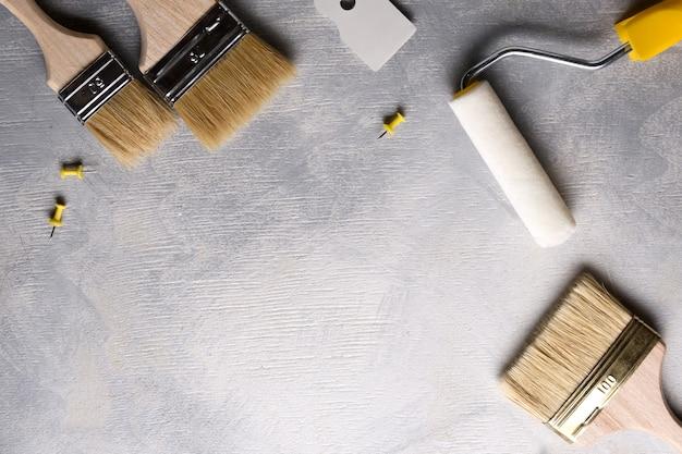 Шпатели для нанесения шпаклевки и кисти и валики для рисования на сером бетонном фоне. вид сверху Premium Фотографии