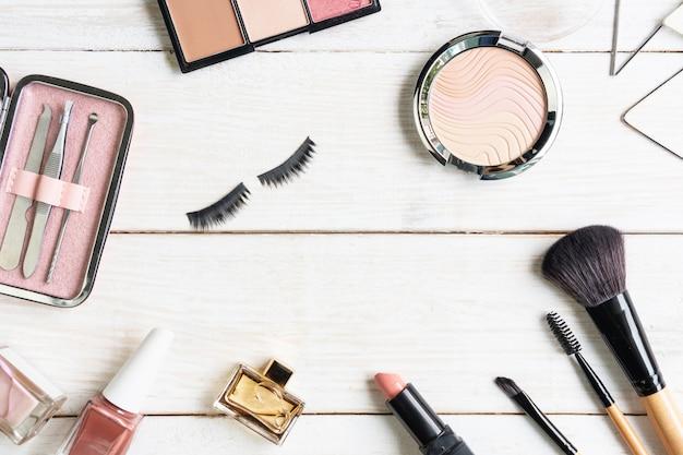 Инструменты и инструменты маникюра в розовом случае с аксессуарами маникюра, косметики и женщин на белой деревянной предпосылке, взгляд сверху, spce экземпляра, концепции красоты. Premium Фотографии