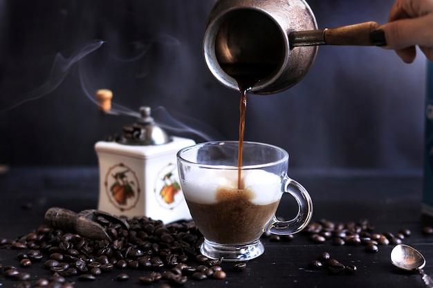 Приготовление ароматного кофе с пеной и молоком. темное фото. турецкий кофе. копировать spce Premium Фотографии