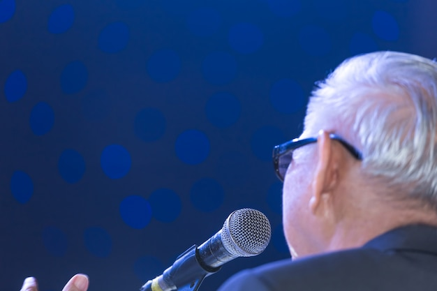 Speaker giving a talk on corporate business conference hall or seminar room background. Premium Photo