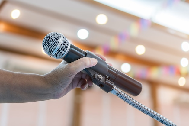 Speaker holding microphone for speak, presentation on stage in public conference seminar room. Premium Photo
