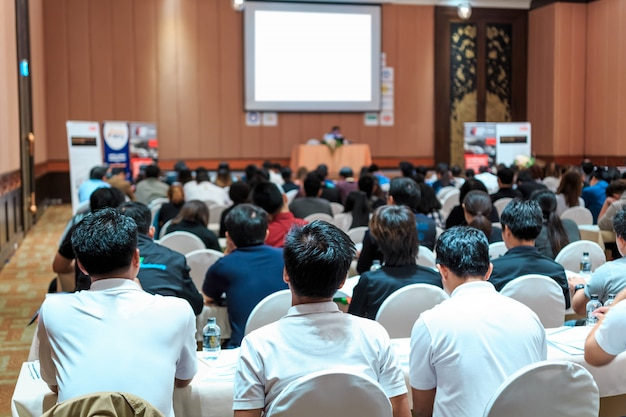 Speakers on the stage with rear view of audience in the conference hall or seminar meeting Premium Photo