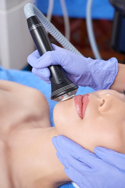 Specialist doing face procedure with instrument Free Photo