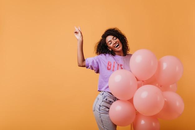 パーティーで目を閉じて笑っている壮大な黒人女性モデル。彼女の誕生日を楽しんでいるかわいいアフリカの巻き毛の女の子。 無料写真
