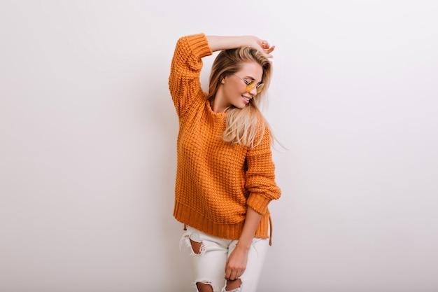 Эффектная блондинка в теплом кардигане позирует перед белой стеной и смотрит в сторону Бесплатные Фотографии