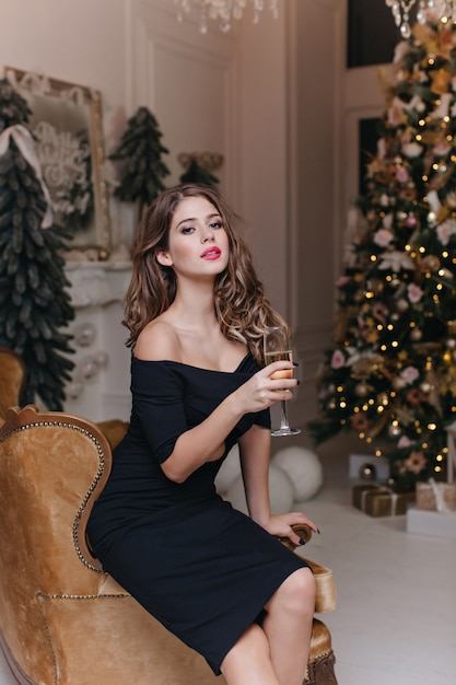 검은 색 드레스를 입은 화려한 곱슬 갈색 머리의 여성이 벨루어 베이지 색 의자에 앉아 새해 분위기에서 맛있는 샴페인 한 잔을 즐깁니다. 무료 사진