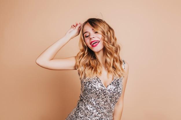 그녀의 생일에 밝은 벽에 춤추는 밝은 화장과 화려한 여성 모델 무료 사진