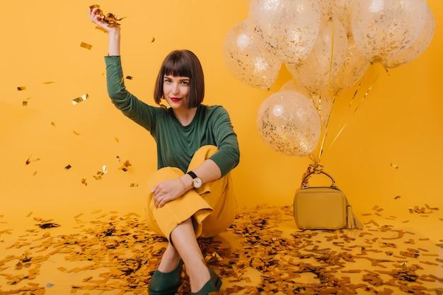 Эффектная девушка весело во время вечеринки. крытый портрет расслабленной женщины брюнет в винтажной одежде. Бесплатные Фотографии