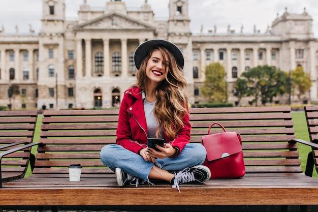 Spettacolare signora con acconciatura alla moda seduta sui gradini di fronte al vecchio edificio storico Foto Gratuite
