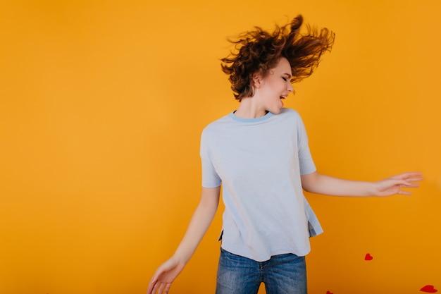 기쁨과 함께 춤을 추는 하늘색 티셔츠에 화려한 짧은 머리 소녀 무료 사진