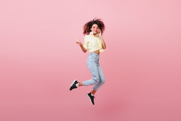Spectacular sporty woman with brown skin dancing with happy face. adorable mulatto girl in black sneakers expressing positive emotions. Free Photo