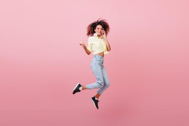 幸せそうな顔で踊る茶色の肌を持つ壮大なスポーティな女性。ポジティブな感情を表現する黒いスニーカーの愛らしいムラートの女の子。 無料写真
