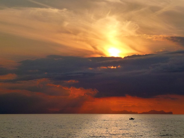 Эффектный закат с красным небом и облаками над морем менорки в испании с силуэтом лодки на ярком отражении солнца на воде Premium Фотографии