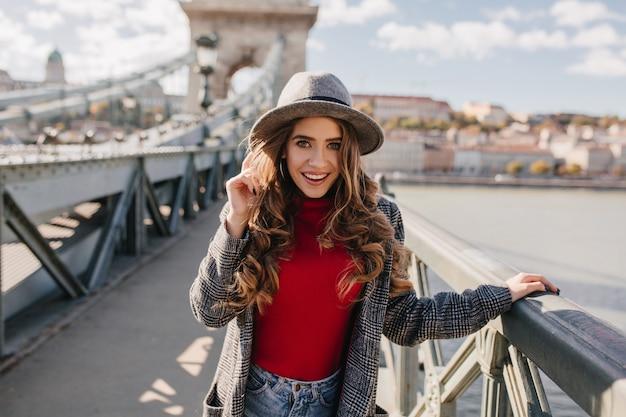 Spettacolare modello femminile bianco in cappello in posa sullo sfondo del fiume e sorridente Foto Gratuite